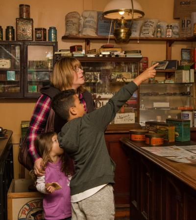 Family in old groceries shop at Milton Keynes Museum