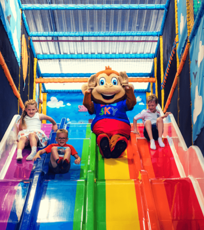 Kids and monkey mascot racing down a four-lane slide at Big Sky Adventure Play