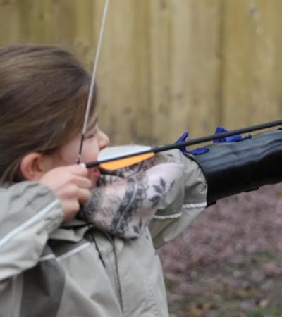Girl doing archery at Beaudesert Outdoor Activity Centre in Rugeley