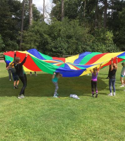 Kids with rainbow play parachute at Northampton Trampoline Centre