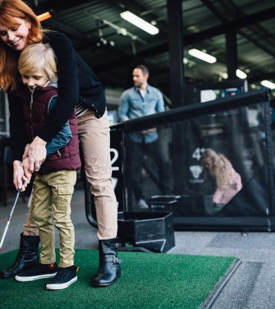 A parent and kid playing golf at TopGolf Surrey, Addlestone