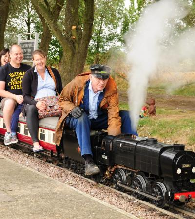 People on miniature train at Summerfields Miniature Railways in Bedford