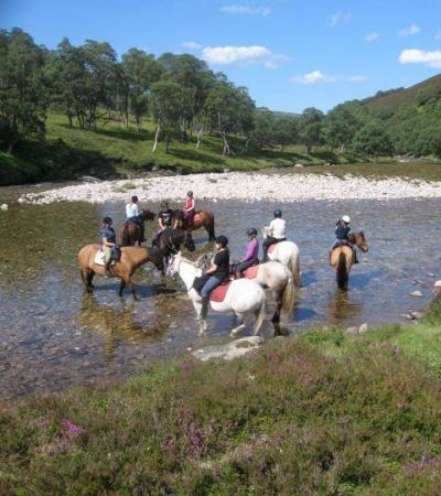 People riding horses in river at Tomintoul Riding Centre
