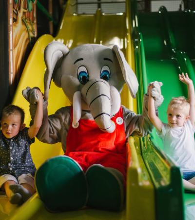 Kids slide down with a mascot elephant at the wild ones soft play in Staffordshire