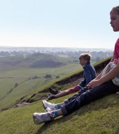 Two kids sat on a side of a hill at Ilam Park, Dovedale and the White Peak