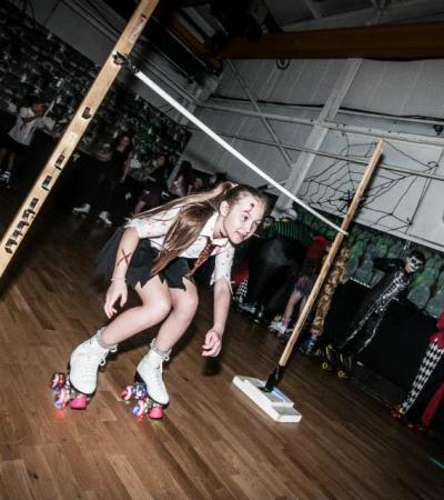 Girl playing limbo on rollerskates at The Skate Station in Ashton under Lyne