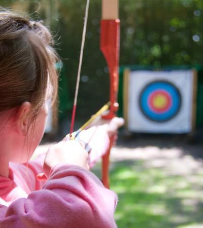 Girl doing archery at Avon Tyrrell Outdoor Centre in Bransgore