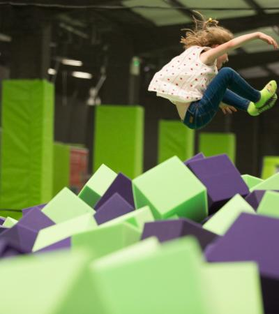 Girl jumping into foam pit at Jump Giants in West Thurrock