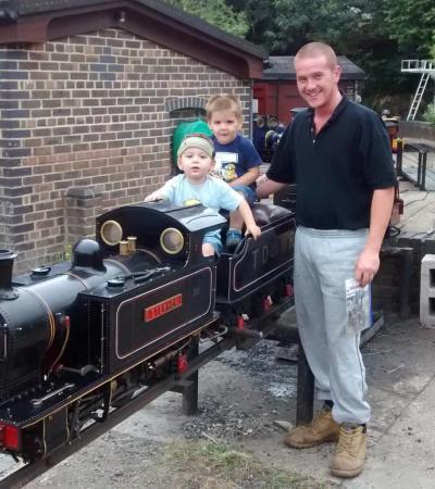 Family by miniature train at Thames Ditton Miniature Steam Railway