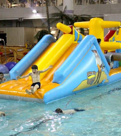 Boy on inflatable slide on pool at Tandridge Leisure Centre in Oxted