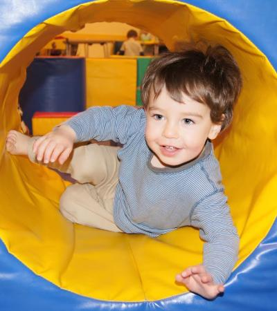 Boy in soft play tunnel at Gym Jams Baby and Toddler Softplay in Guildford
