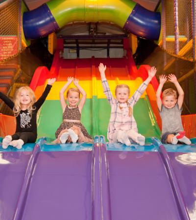 Four happy children sliding down a rainbow slide