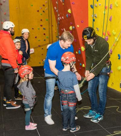 Young kids looking excited as they're strapped into gear and ready to climb at Alter Indoor Climbing and Activity Centre