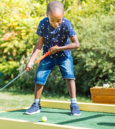 Boy golfing at Plonk Crazy Golf at Horniman Museum in London