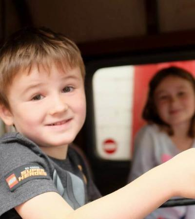 Boy behind the steering of a vehicle at the National Emergency Services Museum