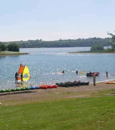 People windsurfing on lake at Carsington Sports and Leisure in Ashbourne