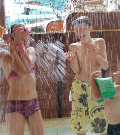 Kids under artificial waterfalls at The Rapids in Romsey