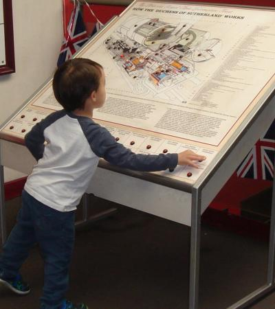 Boy on interactive displays at West Shed Museum in Ripley
