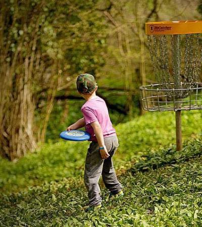 Boy playing frisbee golf at Mendip Activity Centres in Churchill