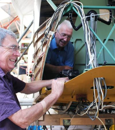 Men fixing aircraft at De Havilland Aircraft Museum in London Colney