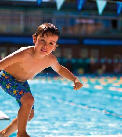 Boy jumping into outdoor swimming pool at Hornchurch Sports Centre