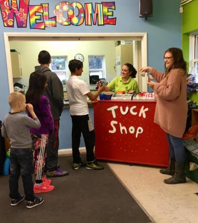 Kids queue for indoor tuck shop at Creasys Drive Adventure Playground in Crawley
