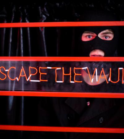 Person in mask looking through sign that says 'Escape The Vault'
