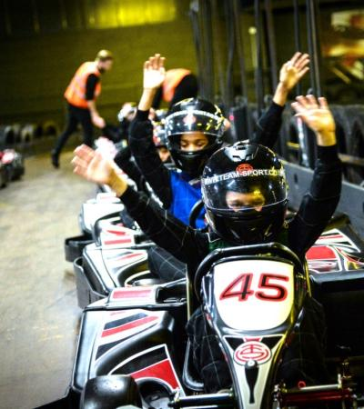 A group waving in the karts at Scotkart in Clydebank