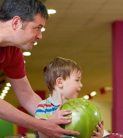 Dad helping son to bowl at Tenpin