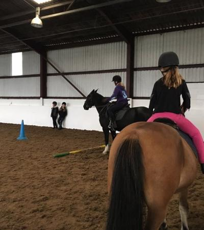 Girls riding horses at Colmar Farm Riding School in South Weald