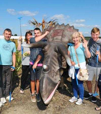 People with mini golf clubs at Dinosaur Escape in Northolt