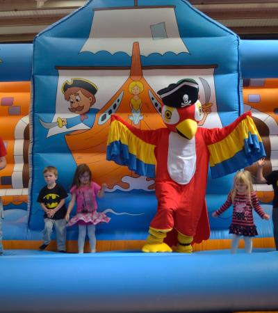 Bird mascot on bouncy castle with kids at Jolly Roger Adventure in Swindon