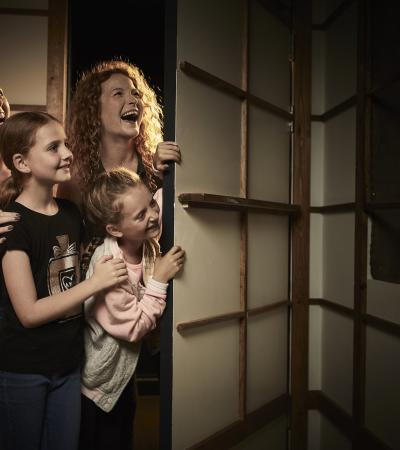 A family looking around a corner at an Escape Hunt room