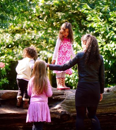 Girls playing on log at Kew Gardens in Richmond