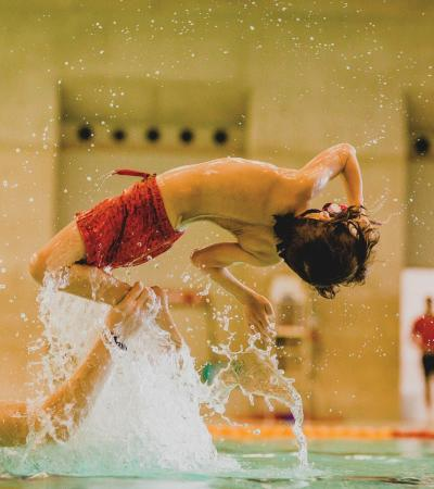 Boy flipping in swimming pool at London Aquatics Centre in London