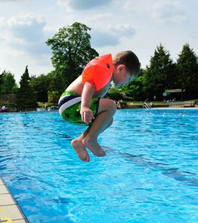 Boy jumping in pool at Guildford Lido