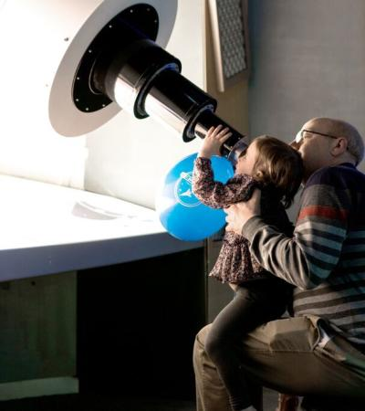 Dad and daughter looking into telescope at National Space Centre in Leicester