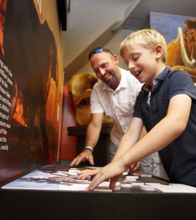 Dad and son doing puzzle at Dinosaur Museum in Dorchester