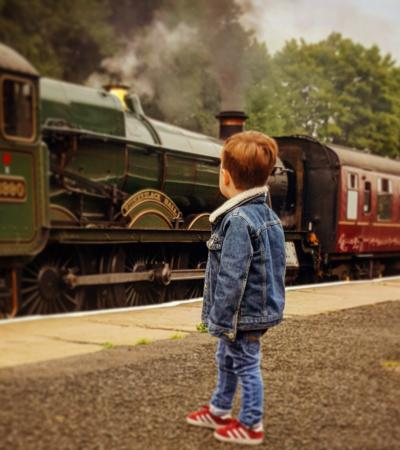 A little boy looking at a train at East Lancashire Railway in Bury