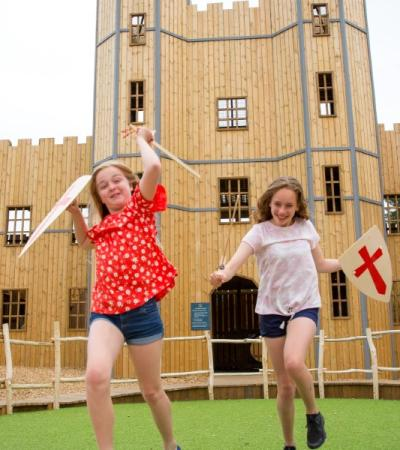 Two little girls at Leeds Castle with toy swords and shields