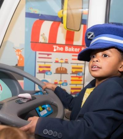 Boy driving bus at London Transport Museum in Covent Garden