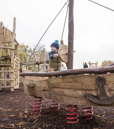 Boy on adventure playground at Willen Lake and Park in Milton Keynes