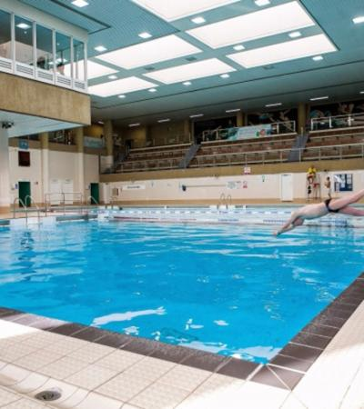 Person diving into swimming pool at Regional Fitness Swimming Centre in Peterborough