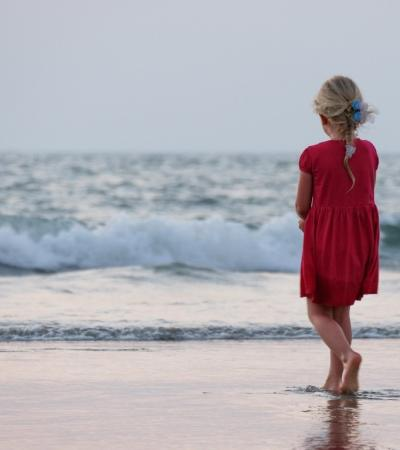 Girl standing on a sandy beach