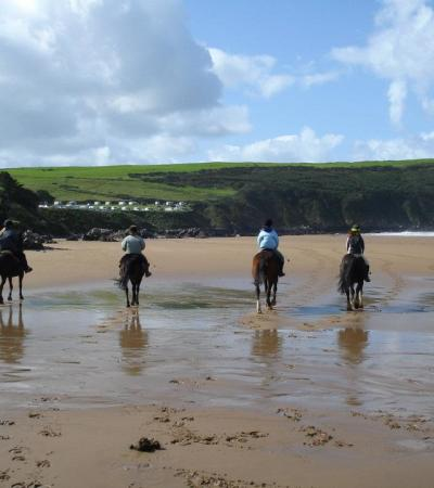 People horse riding on beach at Roylands Riding Stables in Croyde