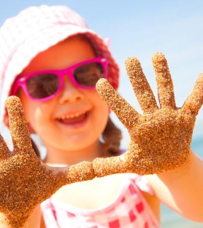 A girl showing her hands covered in sand