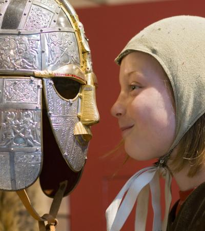 A girl rubs her nose against an ancient warriors battle helmet.