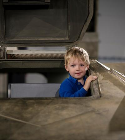 A young boy pops his head out of the tanks hatch at REME Museum