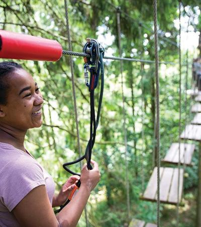 Little girl up smiling on the highropes at Go Ape Wendover