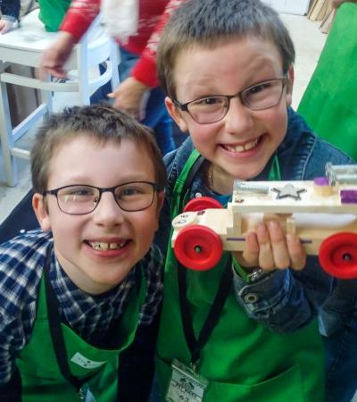 Two boys holding a car they made at Ash & Co Workshops in Crondall